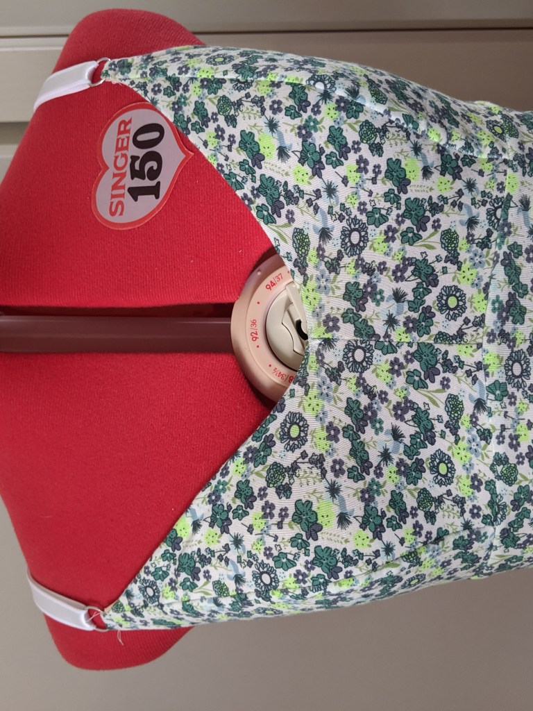 A dressform shows a completed Poppy Bralette, size 8E, in floral cotton spandex.