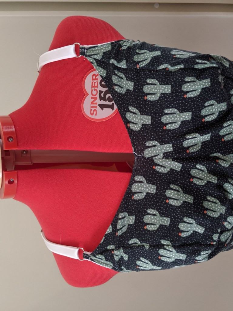 A dressform show a completed Poppy Bralette in size 8, F/G cup, with raised neckline., in cactus print cotton spandex.