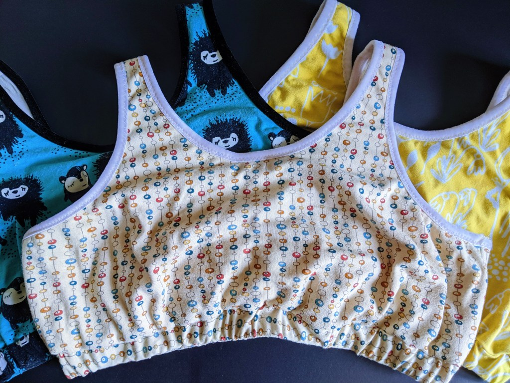 Monserrat's three Banksia bralettes laid flat on a surface. They're all colourful fabrics with cute prints!
