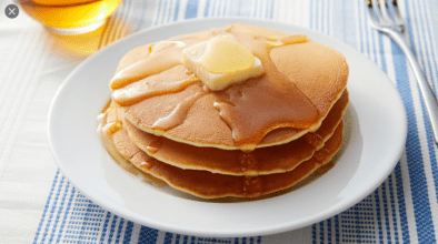 A stack of three pancakes sit on a plate, with butter and syrup.