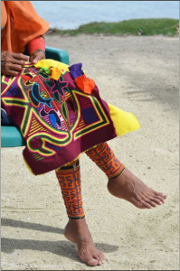 A partial view of a Gunadule woman's lower half of her body. She is sitting in a plastic chair on a beach with her legs crossed. She is working on a colorful mola piece, with outlined shapes of aquatic animals.