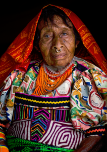 An older Gunadule woman wearing a red cloth with yellow designs over her head, beaded necklaces, and a colorful blouse featuring a mola on the bodice. She has a septum piercing with a gold ring.