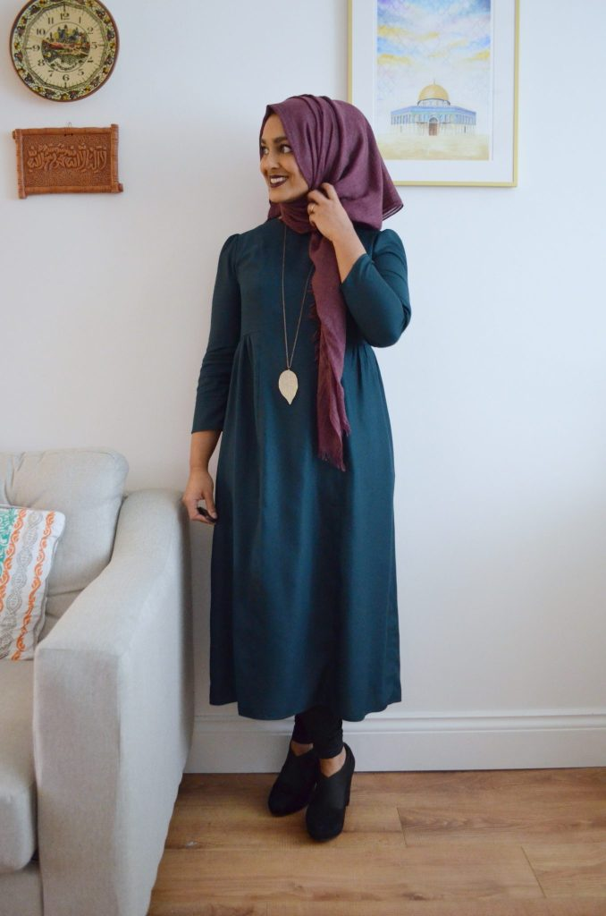 Photo of Rumana wearing a blue ankle-length dress with a purple hijab. Rumana is standing in her home, and is looking away from the camera.