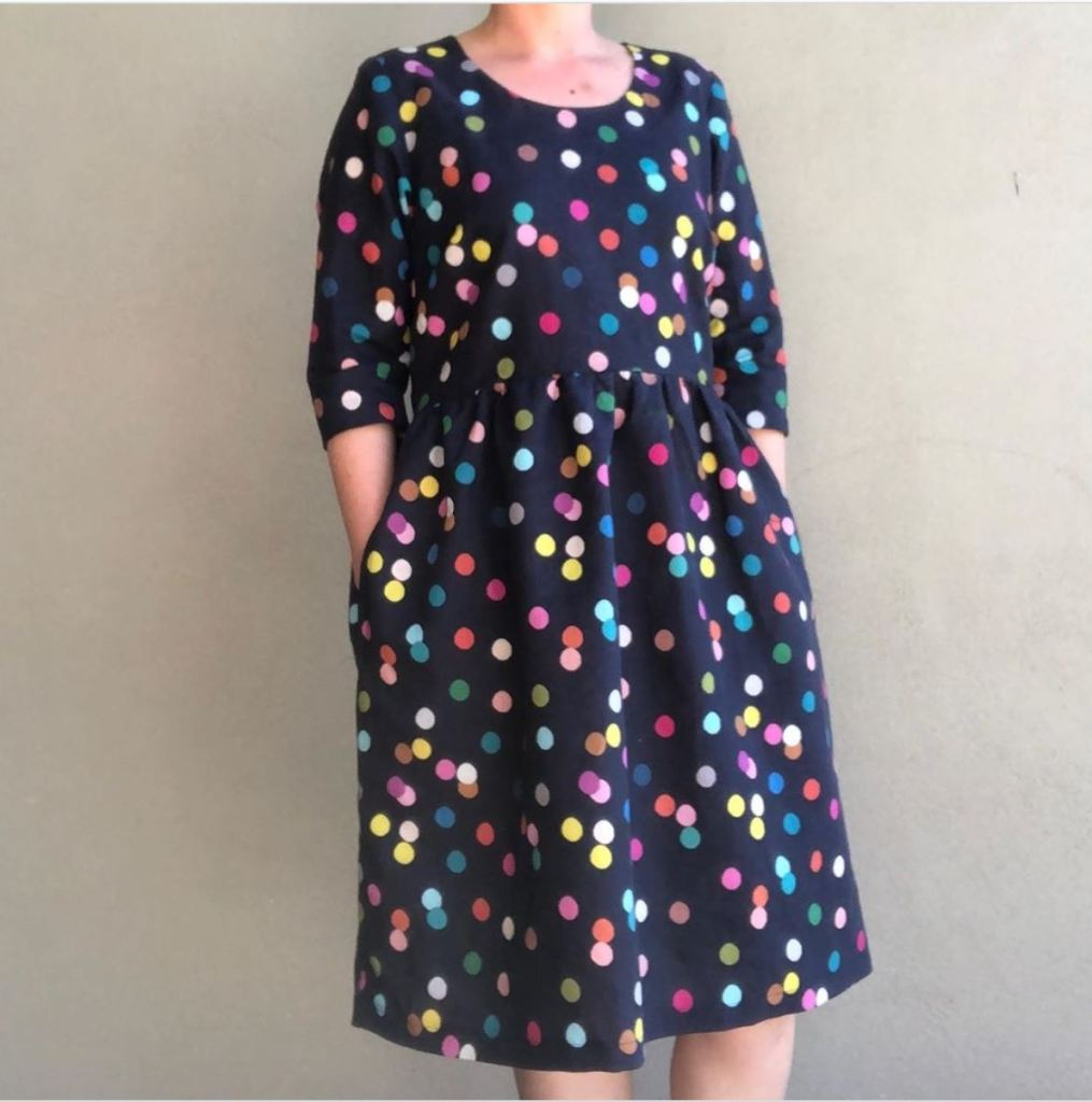 A picture of a person wearing a blue dress with multicoloured spots on it.  Her head is not included in the picture.  Her hands are in her pockets.