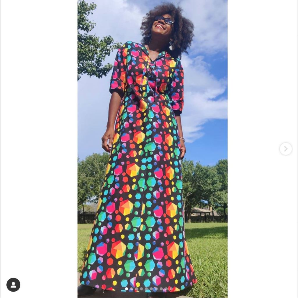A women standing outside on the grass looking up at the blue sky.  She is wearing a full length dress with rainbow gems on it against a black background.  She is wearing sunglasses.