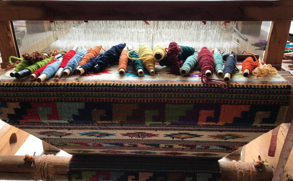 A loom with a part-woven tapete in progress, in a variety of geometric patterns . Around 20 spindles each holding a different  colour yarn lie on the warp threads waiting to be used.