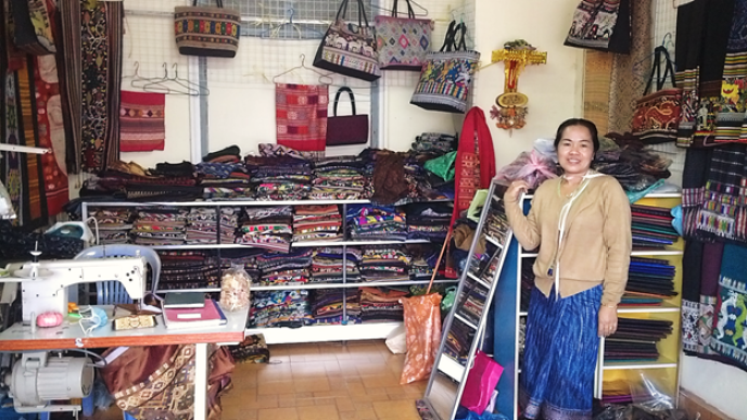 Image of a woman wearing a beige cardigan and blue skirt standing at a fabric stall with colorful bags hanging from the wall and various cuts of colorful fabric neatly folded on shelves