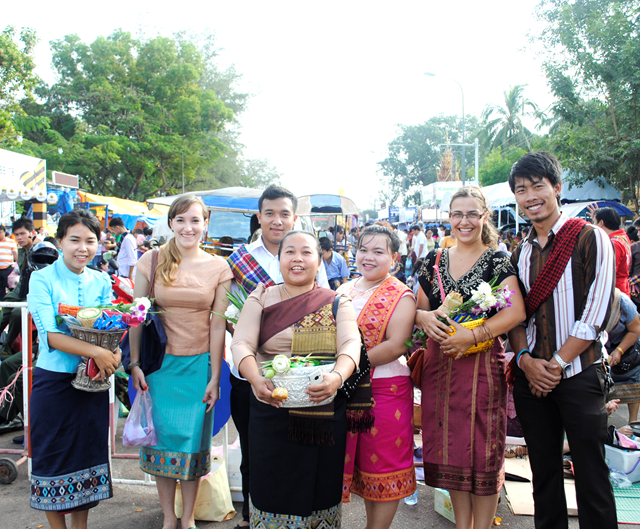 Image of a group of people standing for a picture at an open market. The women are wearing sihns, a cut of fabric sewn into a large circle, which is wrapped around the waist and connected in two spots with hooks