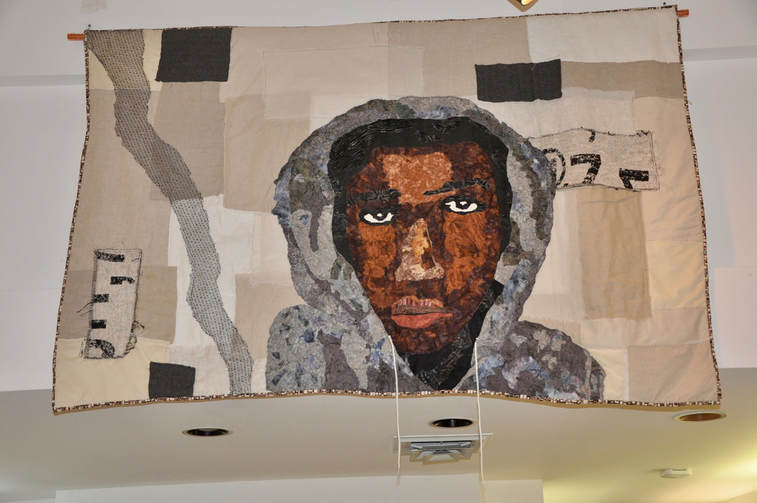 Quilt depicting Trayvon Martin against a cream background.