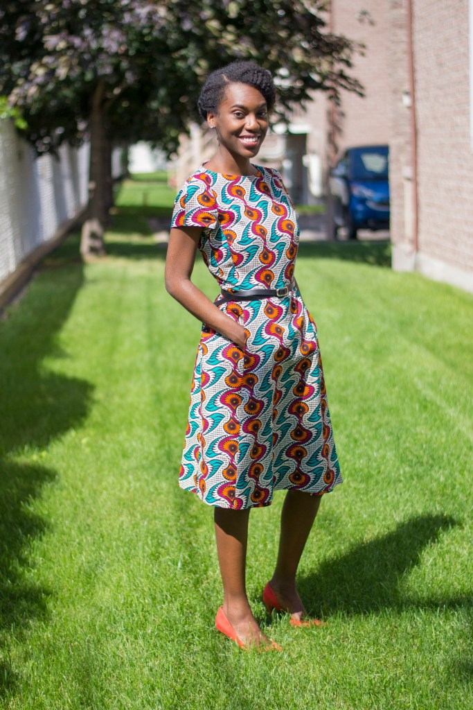 Person in a knee-length dress made of an Ankara print with orange, red, teal and other colors