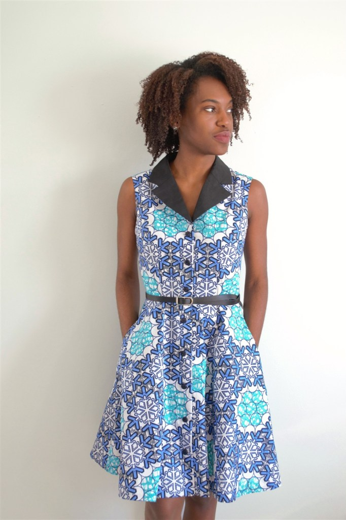 Person in a sleeveless, knee-length dress made of an Ankara print with different blues and other colors