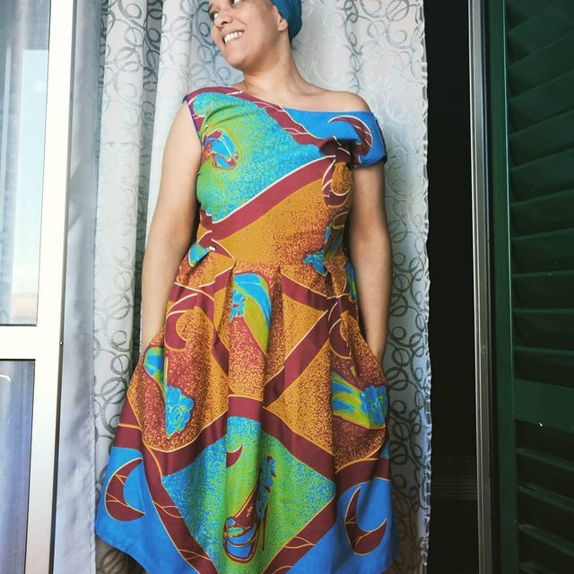 Maggie wearing a colorful dress in orange, blue, green, and orange colors. The dress also has large crescent moon and heel prints on it.