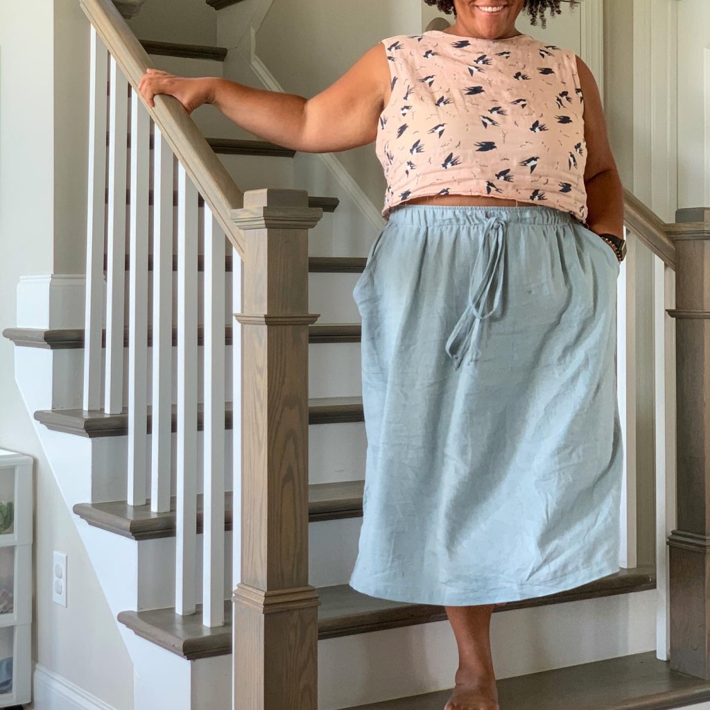 Editor Amanda is standing at the bottom of stairs wearing a midi-length, light blue, elastic-waisted skirt that has a drawstring. She also has on a crop top that is light pink and has birds on it.