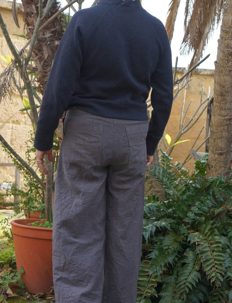 A person stands in a garden wearing grey trousers made from a regular trouser pattern , that has been converted to a zero waste pattern. They are worn with a navy blue sweater.