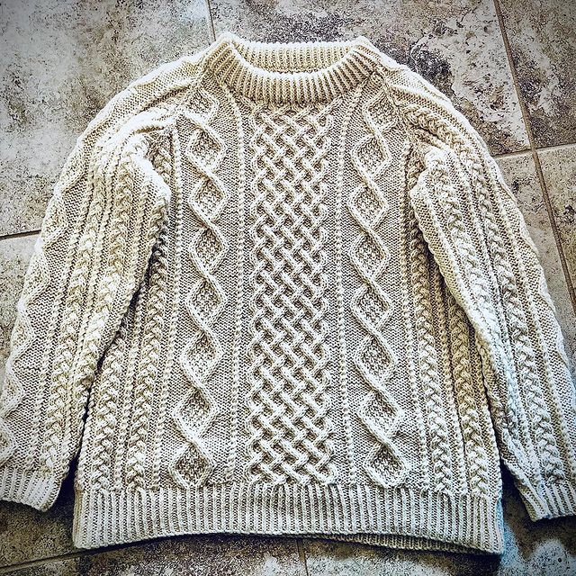 Hand knit cabled pullover in cream yarn, lying flat on a creamy grey floor.