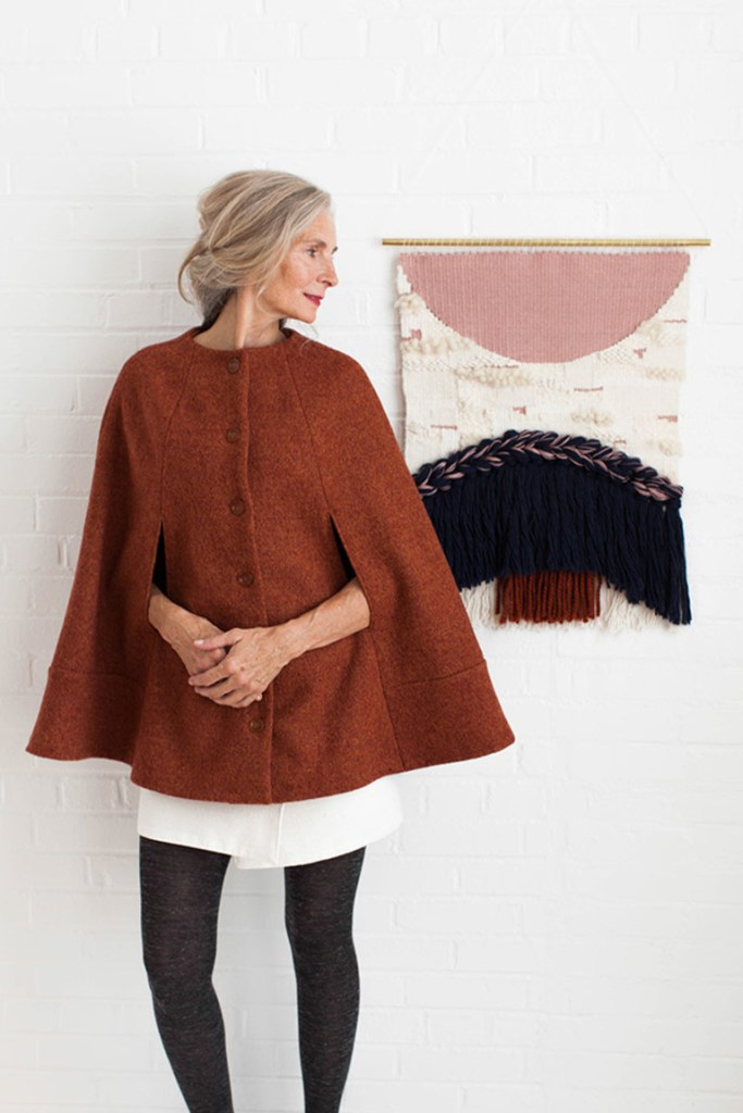 An older white woman stands in front of a wall tapestry wearing a rust colored cape that is closed with 6 buttons.
