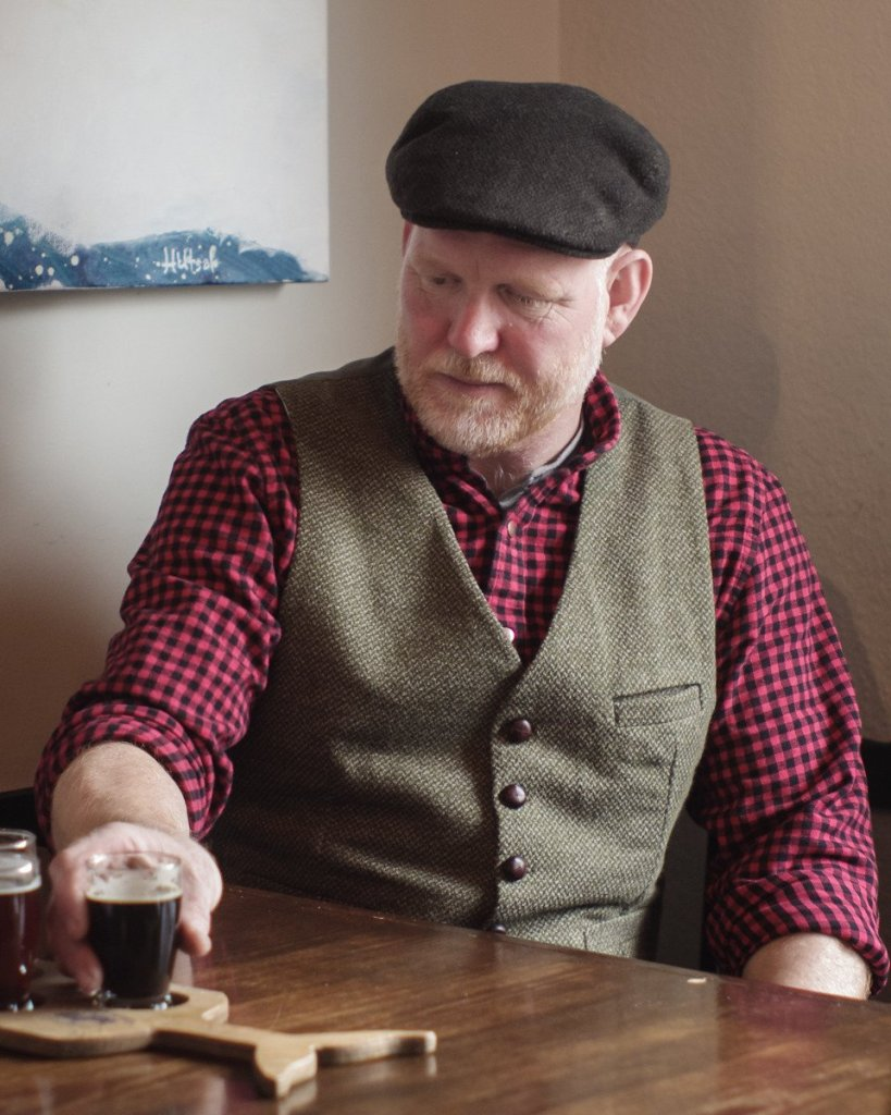 An older white man sits at a bar wearing a buttoned shirt with rolled up sleeves and a waistcoat (vest) over it. The waistcoat has small brown buttons.