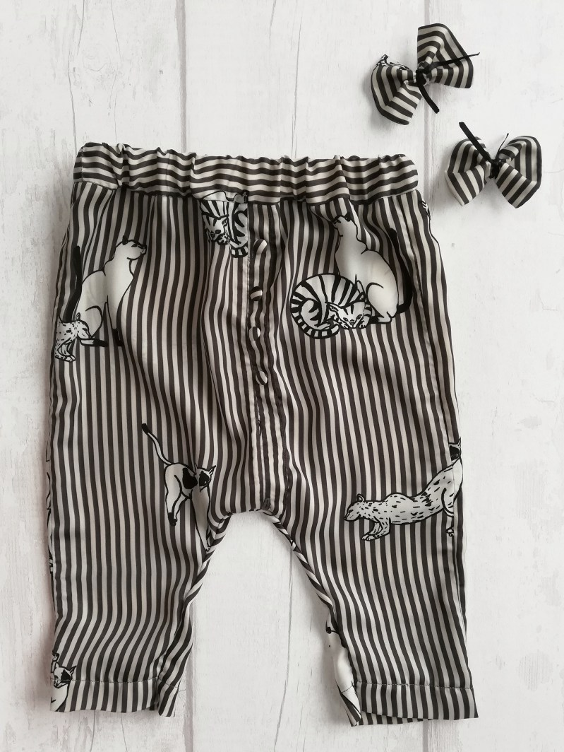 Flatlay photo of children's lounge trousers and two small hair bow clips. All in matching fabric that is black and grey striped with big cat illustrations.