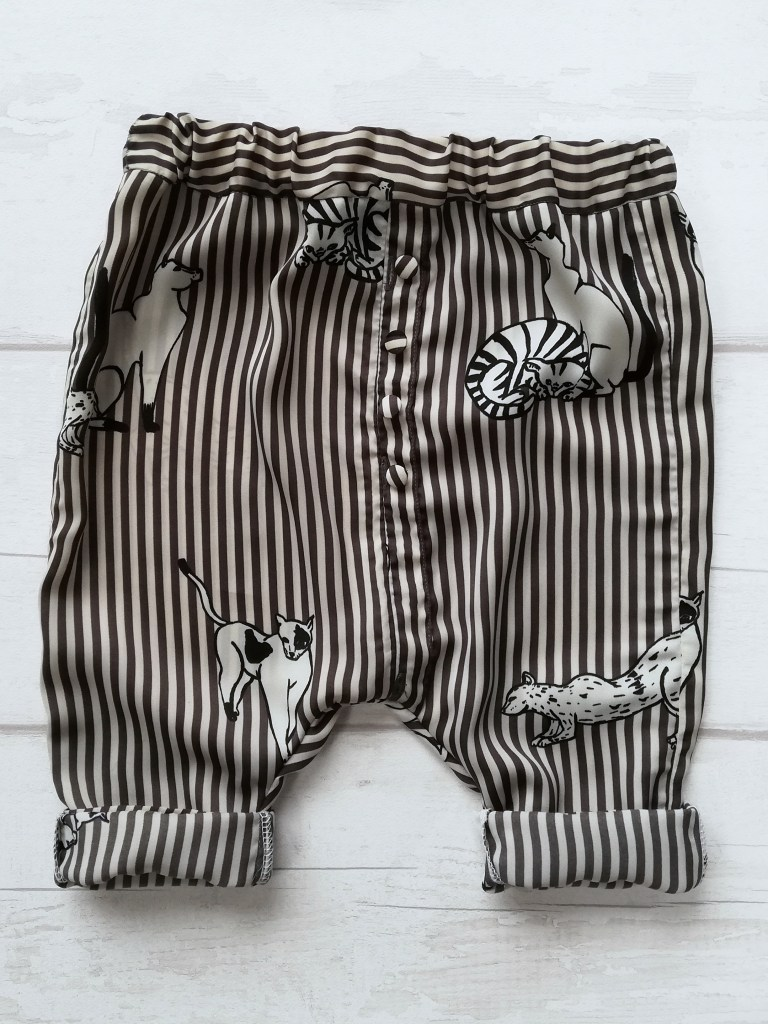 Black and white striped trousers with large cat print laid out flat with the leg cuffs turned up twice. The inside fabric showing on the cuffs is a slightly faded version of the striped outside fabric.