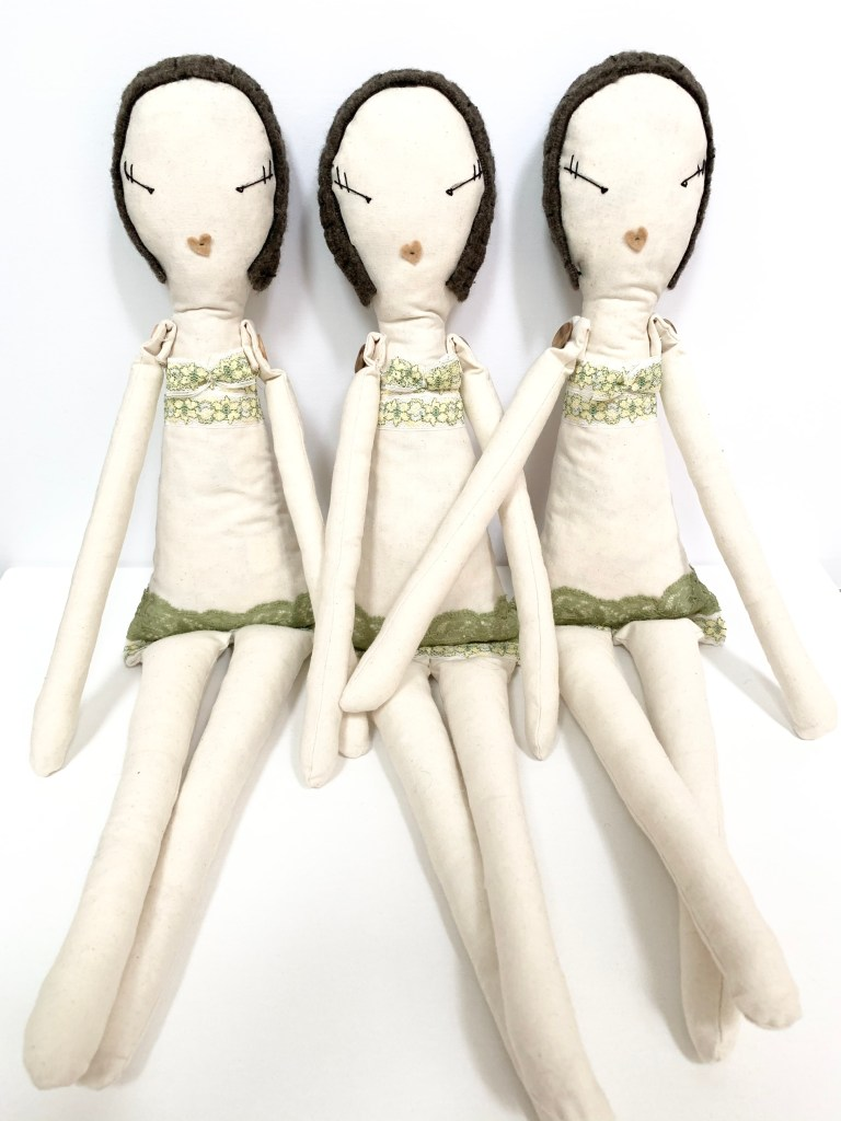 Three dolls sit together, without their dresses, showing the lace trim underwear details.