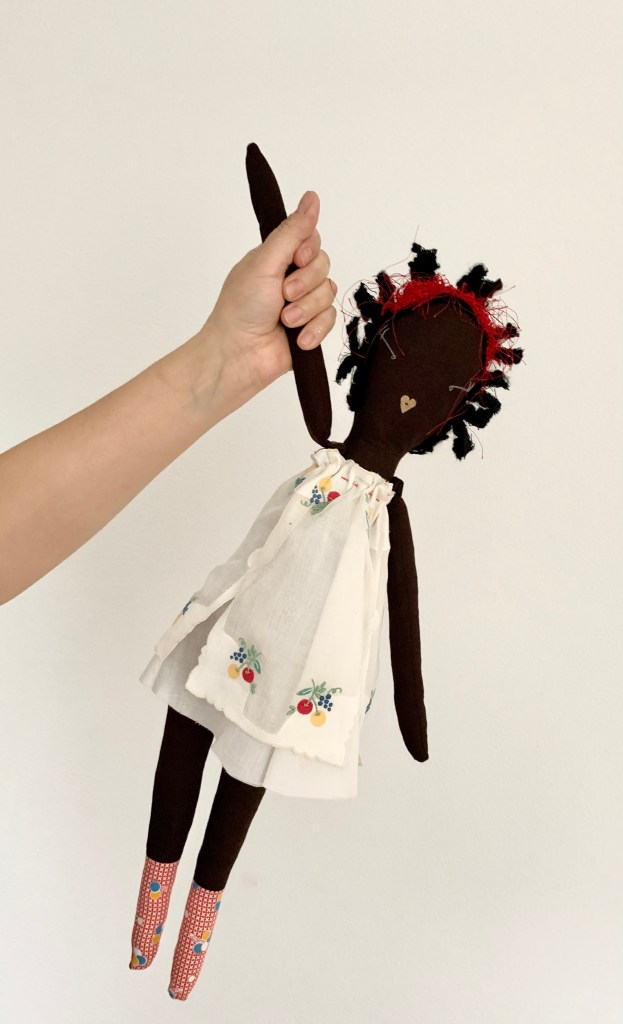 A hand holds a rag doll by it's arm.  The rag doll has a brown fabric body, black wool hair, a white embroidered dress and red check feet.