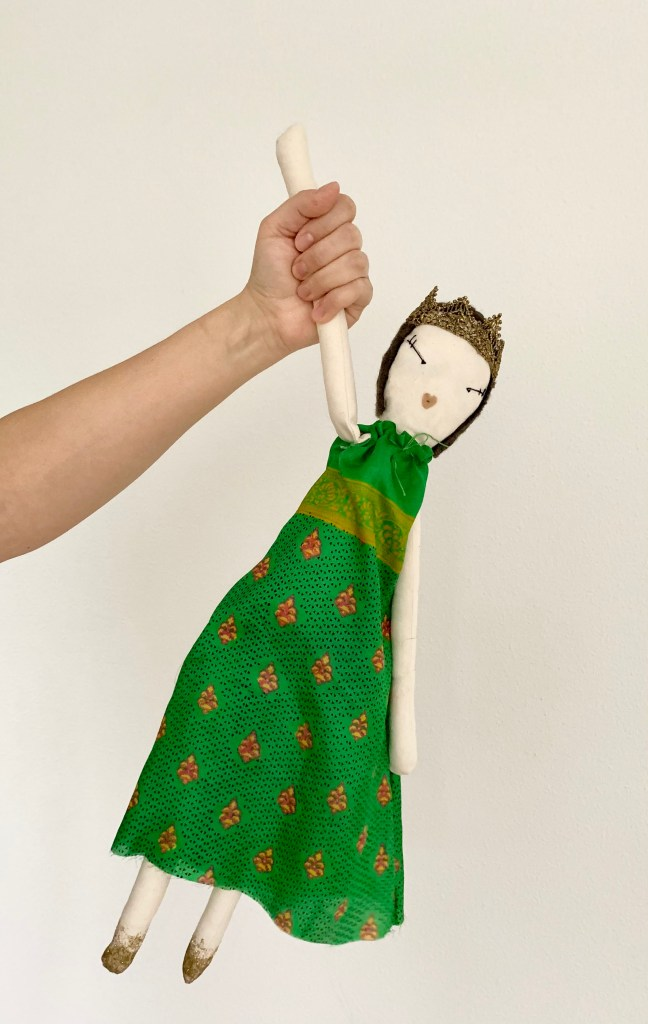 A hand holds a rag doll by it's arm. The doll has a white cloth body, is wearing a green patterned dress, a tiara made from gold trim, and has glitter painted feet.