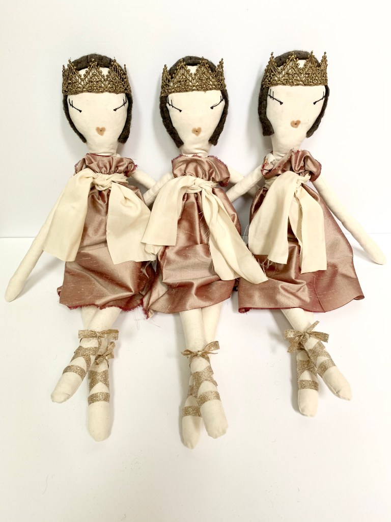 Three dolls as described in the previous image sit together.