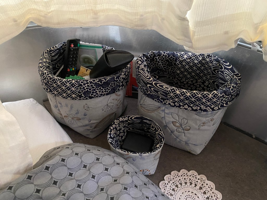 Three fabric storage boxes made from Japanese fabrics. They are grey, blue and cream.