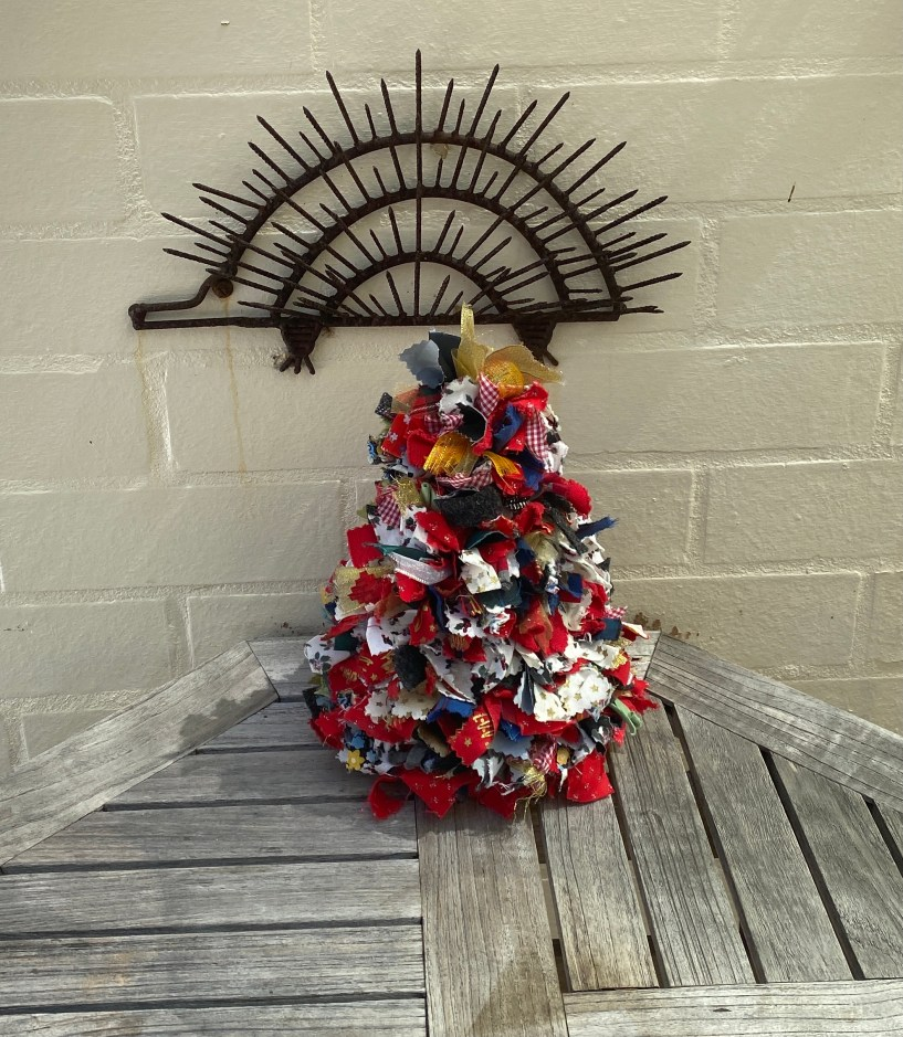 A Christmas tree made from colourful fabrics and ribbons, sitting beneath an echidna made from rusty nails.