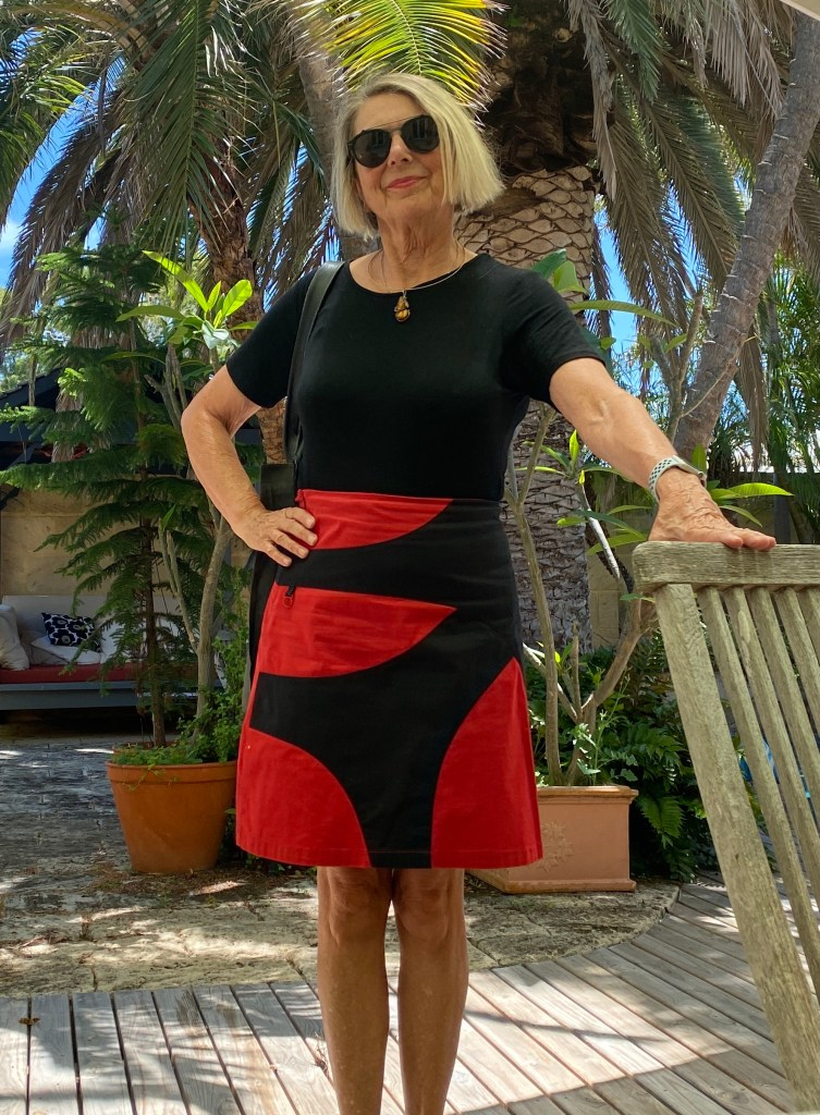 Sue stands in a garden wearing a black t shirt and a red skirt which has random shaped black fabric sewn over the top.