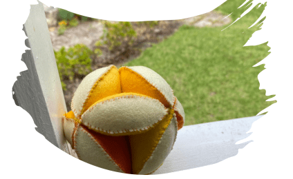 An Amish puzzle ball made from yellow, orange and cream wool felt.