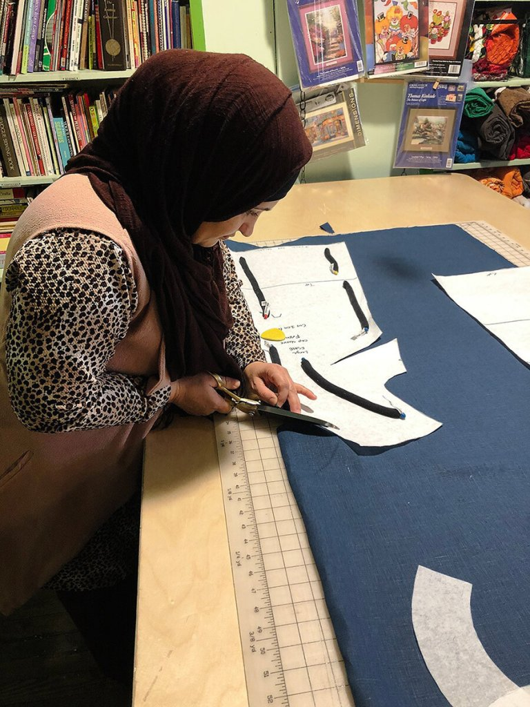 Seamstress Palwasha Basir leans over a table to cut out a pattern from a dark blue fabric.
