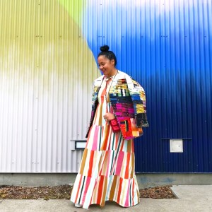 Woman wearing a dress and jacket made from colourful fabric scraps.