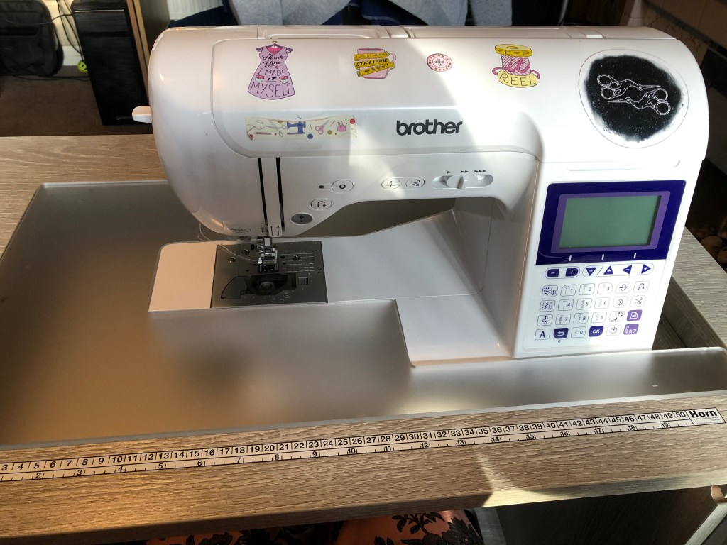 Michelle's Brother sewing machine, with a digital screen and start-stop button. The machine is decorated with cheerful sewing-related stickers.