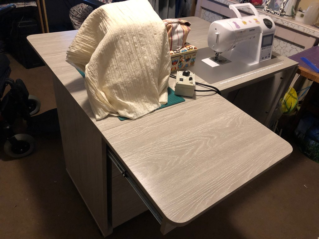 Another shot of the sewing table. This time, the overlocker is still covered, but the computerized machine has been raised into sewing position on the tabletop.