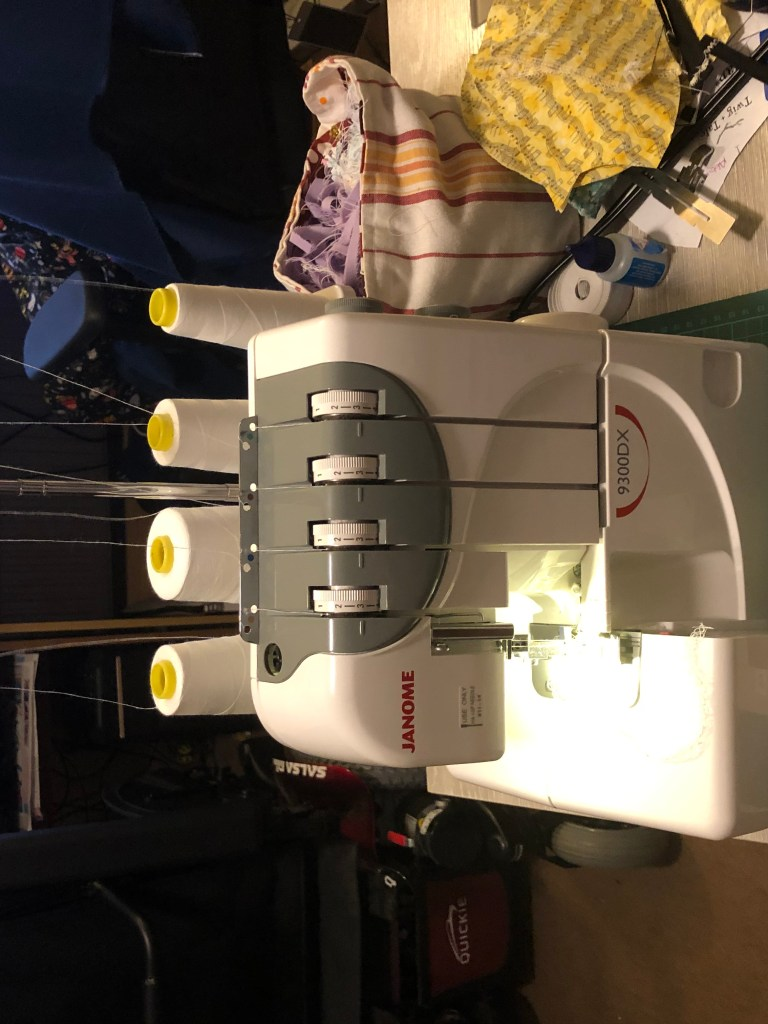 Another shot of the modified serger, showing the control box in front of the Janome machine. There are snips and other tools around the sewing area.