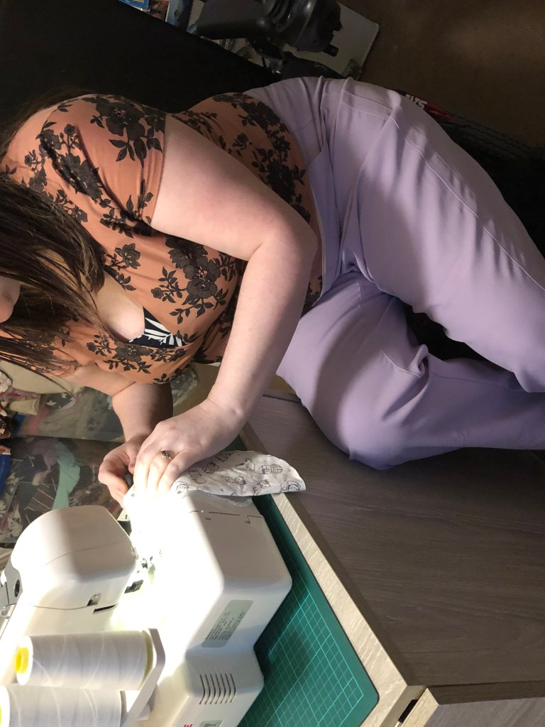 Michelle is sitting down next to their sewing machine. Michelle is wearing a copper top with a black flower print and  lilac pants.