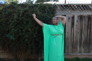 Image of a Black woman with shaved head and glasses standing in front of a tall fence. She is wearing a bright green dress.