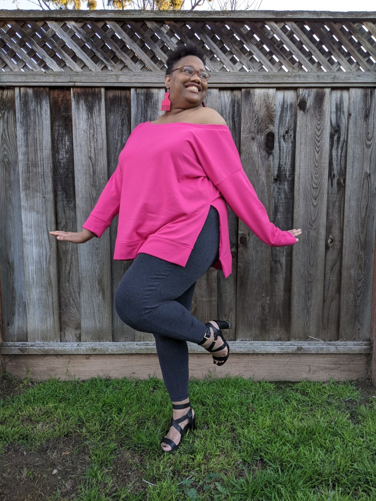 Image of a Black woman with short hair and glasses stands in front of a tall fence. She is wearing a bright pink pair of dangling earrings, an off-the-shoulder bright pink sweater, dark gray pants, and strappy black heels.