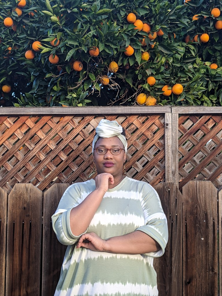 Image of a Black woman wearing a head scarf and glasses sitting in front of a tall fence. Behind her, there is an orange tree full of oranges. She is sitting down, hand to chin, and she wears a tie-dye green and white dress.