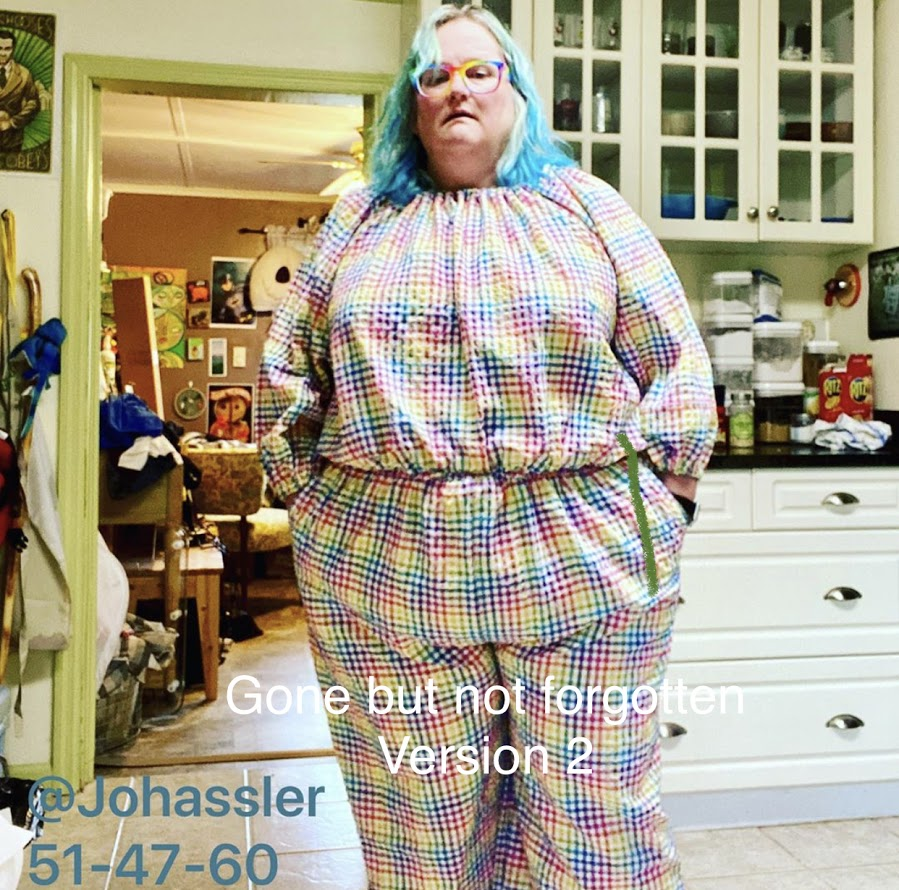 """An unhappy fat white lady is looking at the camera while wearing a jumpsuit that is close fitting at the stomach and hips. It is made from a rainbow plaid seersucker material. Text on the photo states """"Gone but not forgotten"""" and """"version 2""""."""