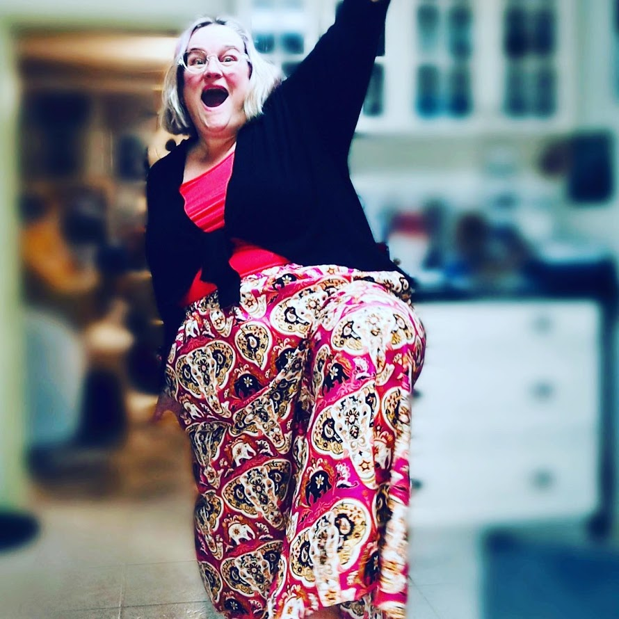 Jenny, a white fat human, stands with one leg in the air, wearing pink patterned wide leg pants and a pink tank top with a black cardigan tied in the front