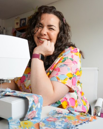 Samantha is sitting in front of her sewing machine. She is wearing a purple watch and a pink, blue, and yellow shirt.