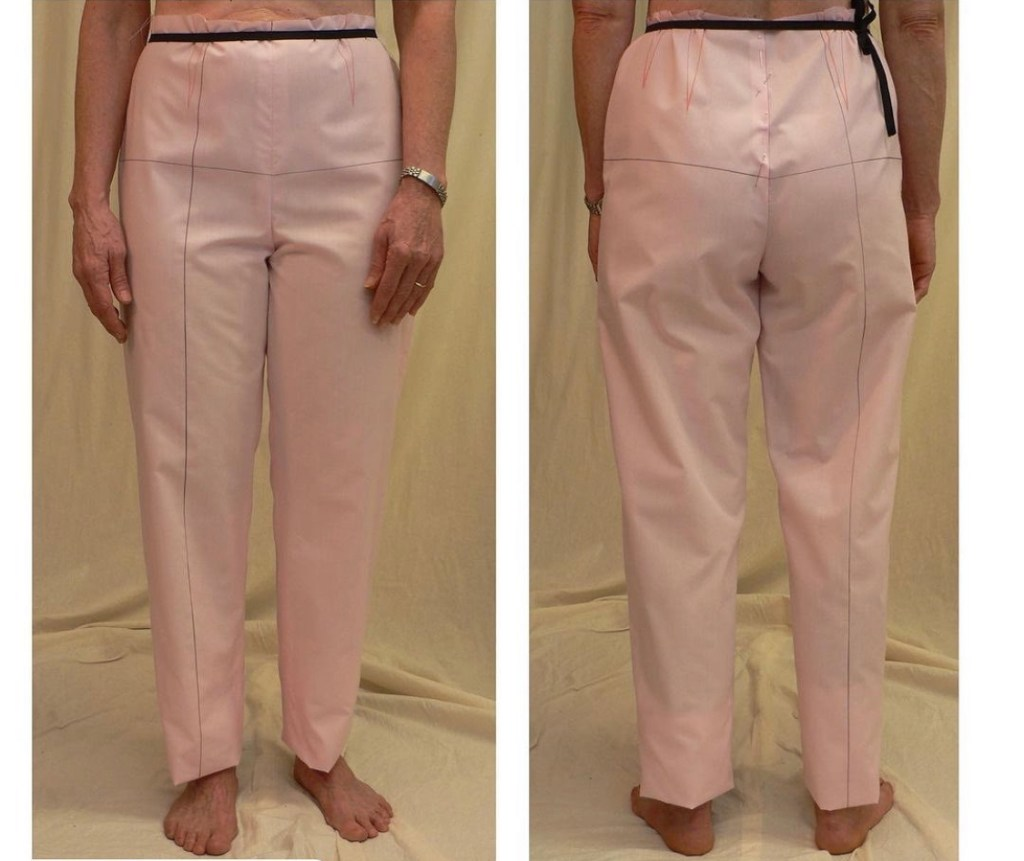 Two images of a person facing  forward and back wearing a marked pants muslin