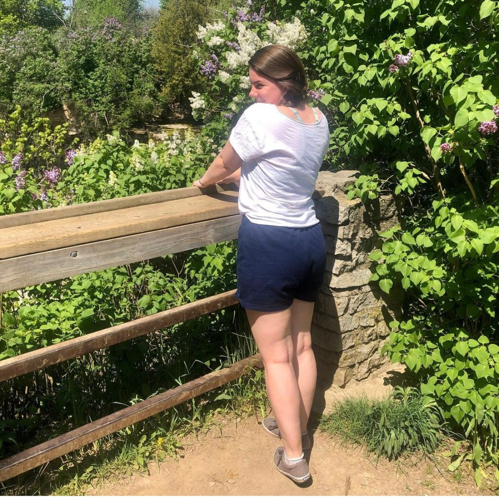 A white woman stands with her back facing the camera. She is showing her butt in navy shorts.