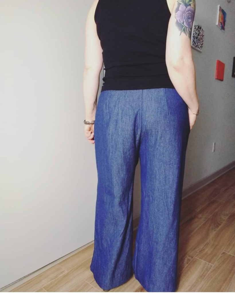 A person wearing a black top and denim-colored pants with their butt to the camera