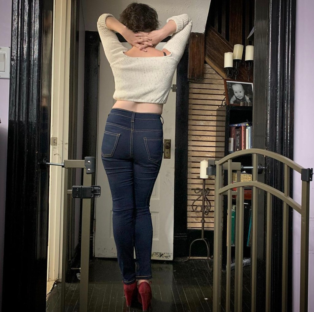 A woman standing facing her back to the camera and showing her butt in jeans