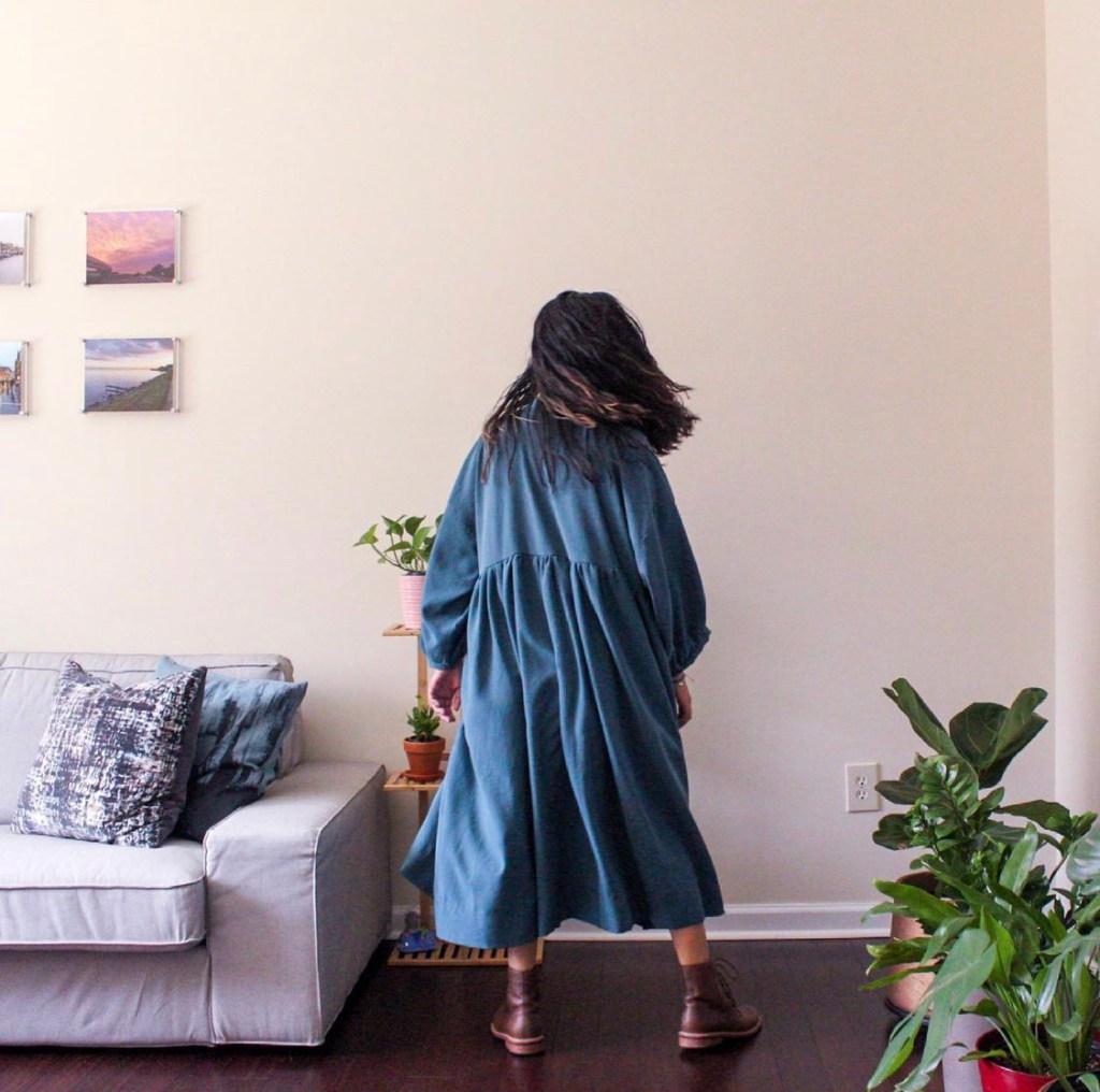 A woman with long dark hair twirls around in a blue zero waste dress