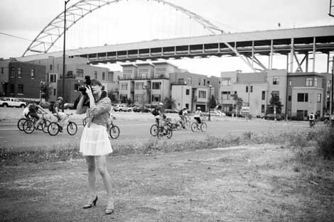 A black and white photo of a woman holding a camera to her face with cyclists in the background