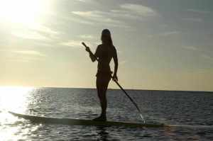 Silhouette of a woman paddle boarding on the ocean.